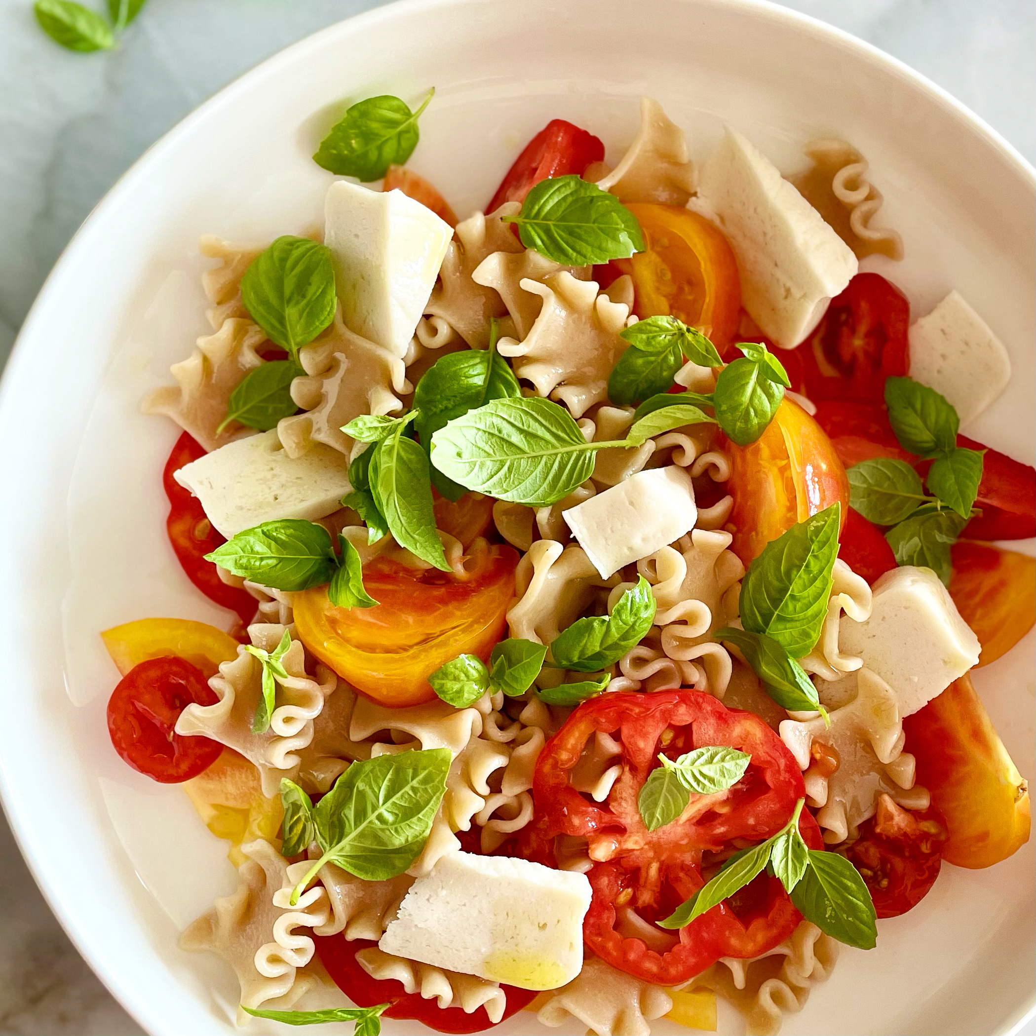 pasta with heirloom tomatoes, plant-based mozzarella, and basil